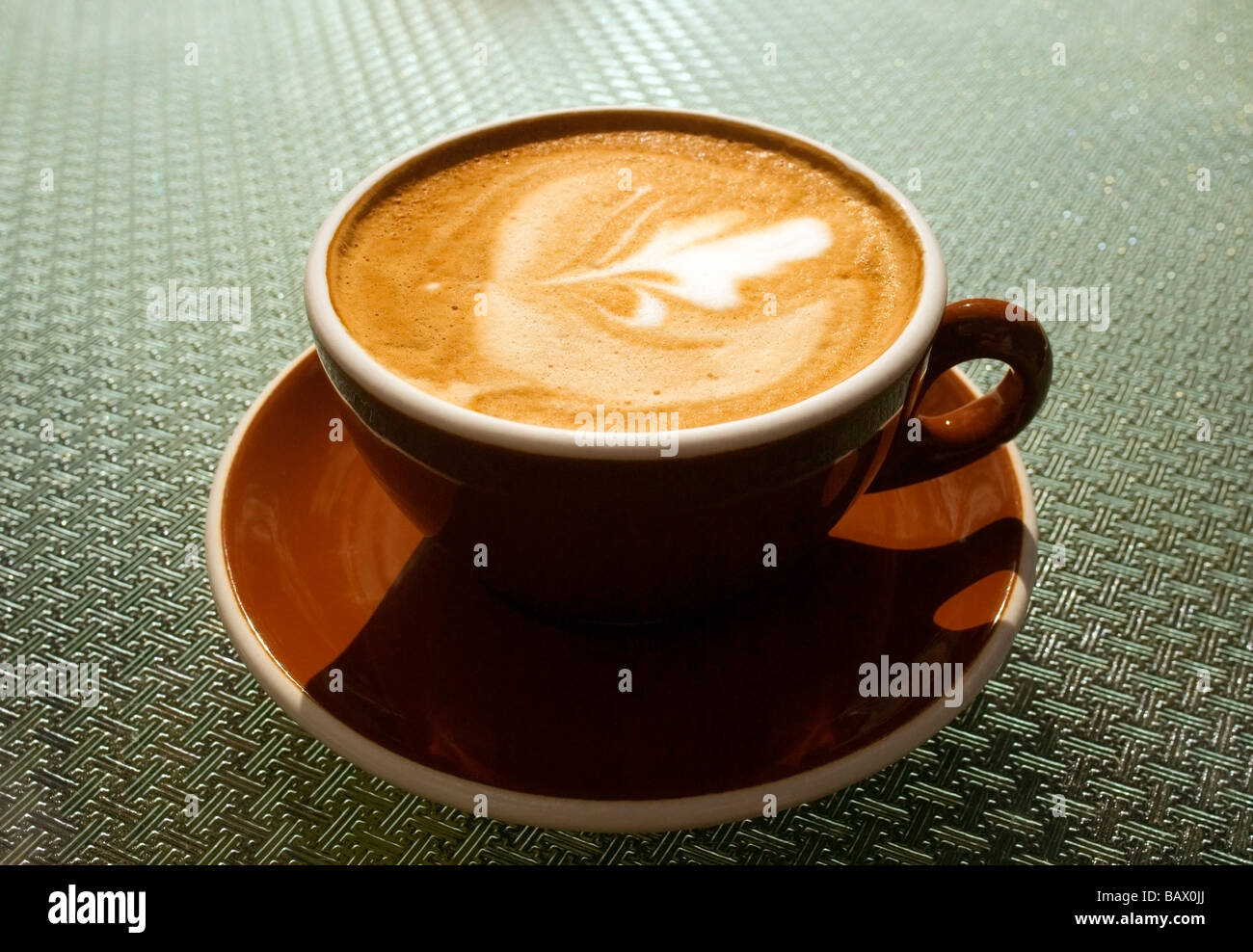 A SINGLE CUP OF COFFEE , KNOWN IN NEW ZEALAND AS A ' FLAT WHITE '  COMPLETE WITH DESIGN IN THE FROTH - Stock Image