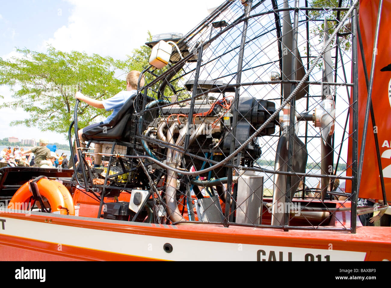 Boy age 12 sitting in drivers seat of fire dept. water rescue airboat. Aquatennial Beach Bash Minneapolis Minnesota - Stock Image