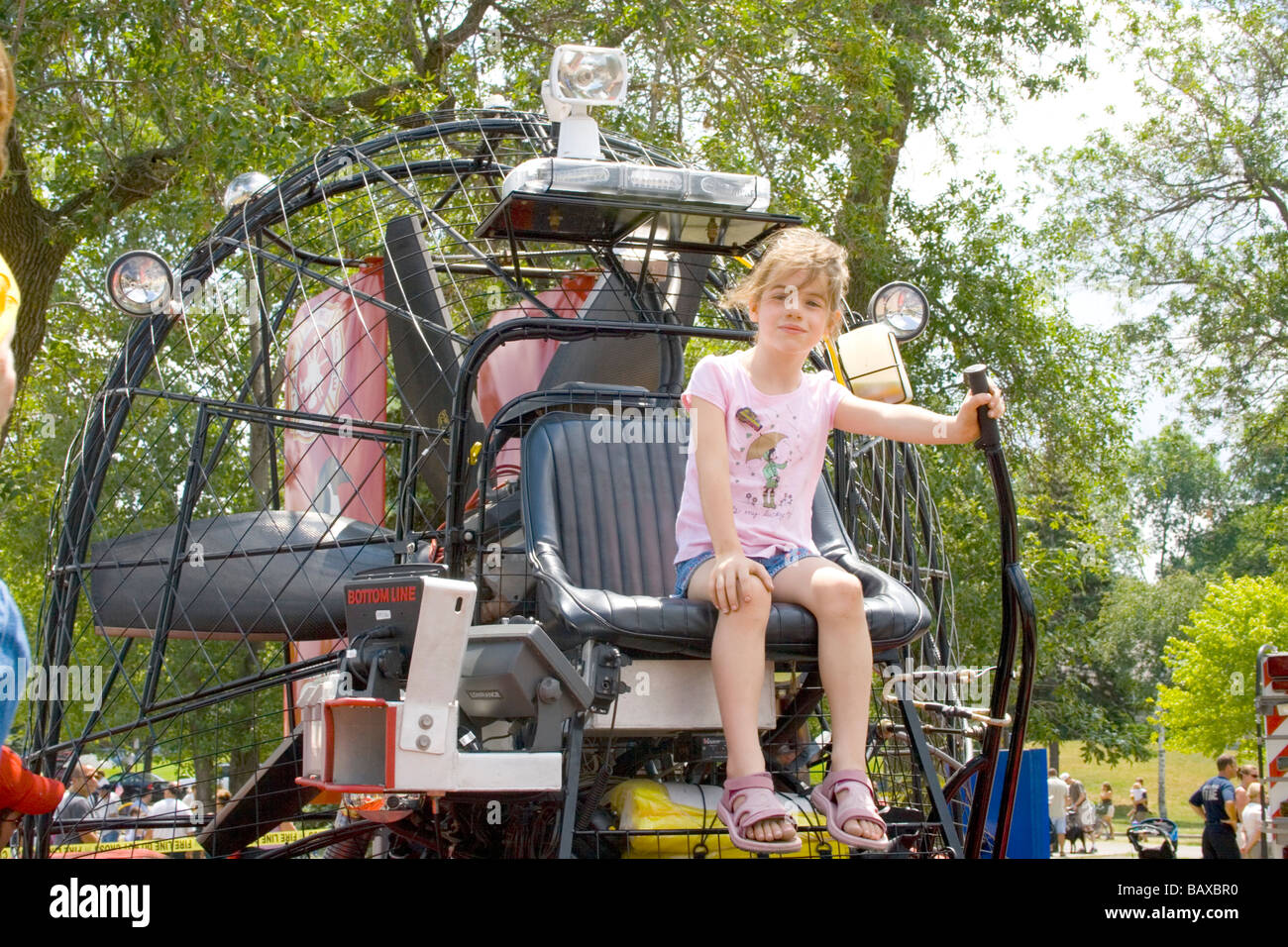 Confident young girl age 6 in drivers seat of fire dept water rescue airboat. Aquatennial Beach Bash Minneapolis - Stock Image