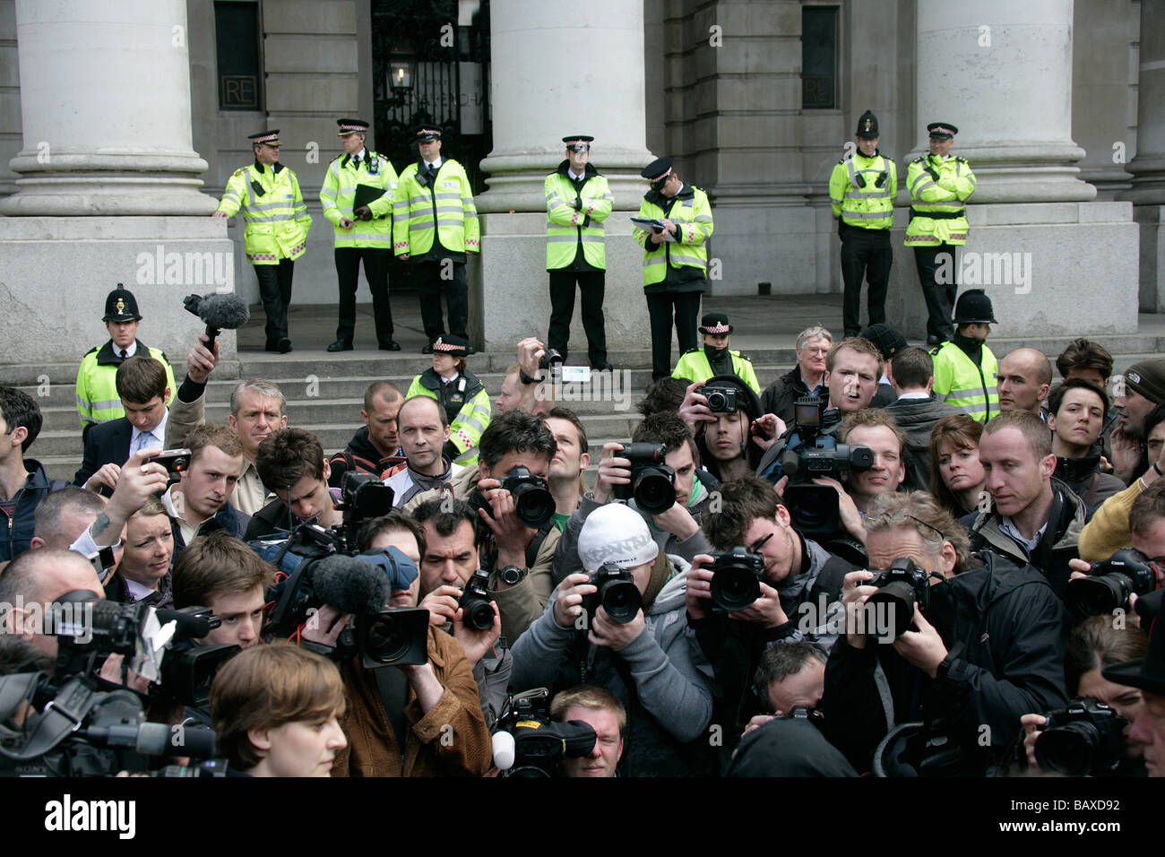 A hoard of news photographers and cameramen covering a news story are watched over by British London Metropolitan - Stock Image