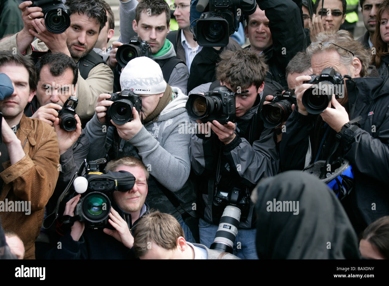 A hoard of news photographers and cameramen cover a news story - Stock Image