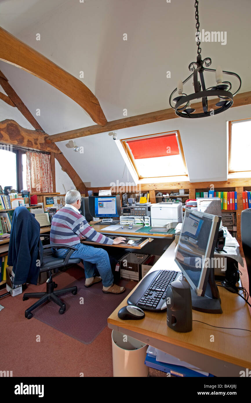 Man sitting working in home based IT computer office above garage in Cotswold house Woodmancote UK - Stock Image
