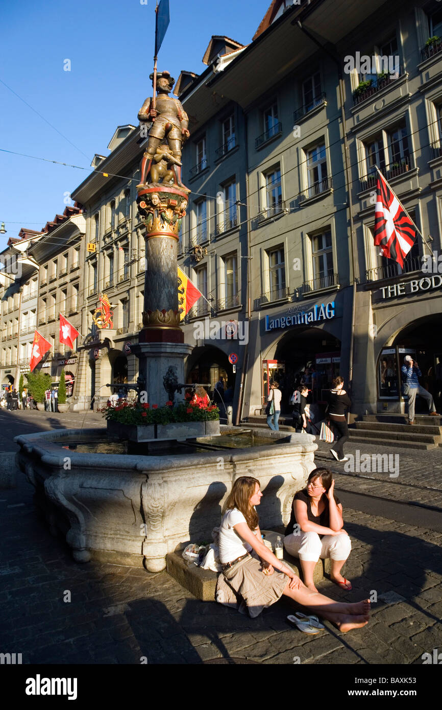 Two young women siting in front of a fountain, Schuetzenbrunnen, Marktgasse, Old City of Berne, Berne, Switzerland - Stock Image