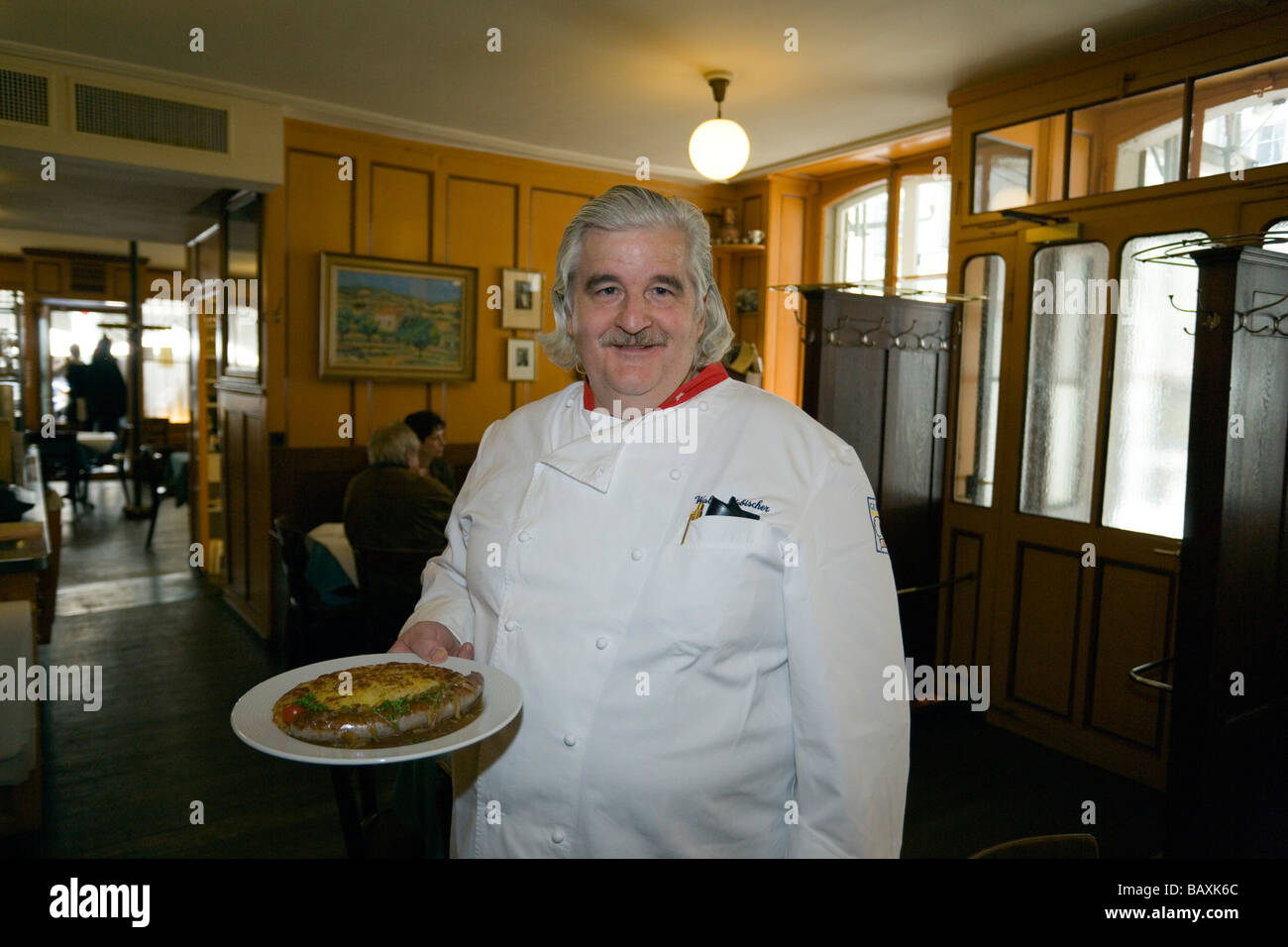 A chef holding traditional food, Restaurant Harmonie, Old City of Berne, Berne, Switzerland - Stock Image