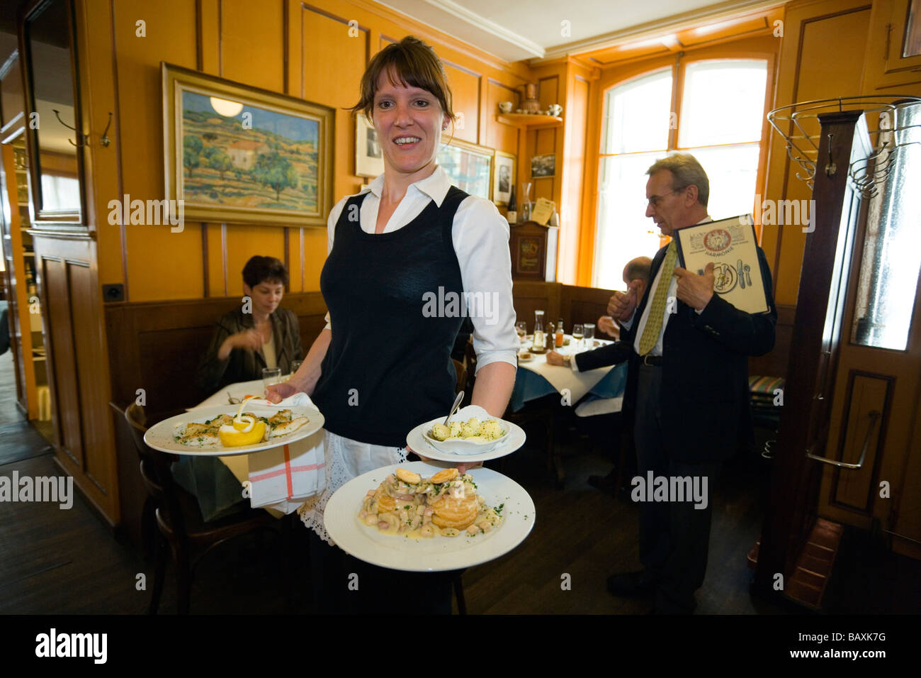 A waitress carrying traditional food, Restaurant Harmonie, Old City of Berne, Berne, Switzerland - Stock Image