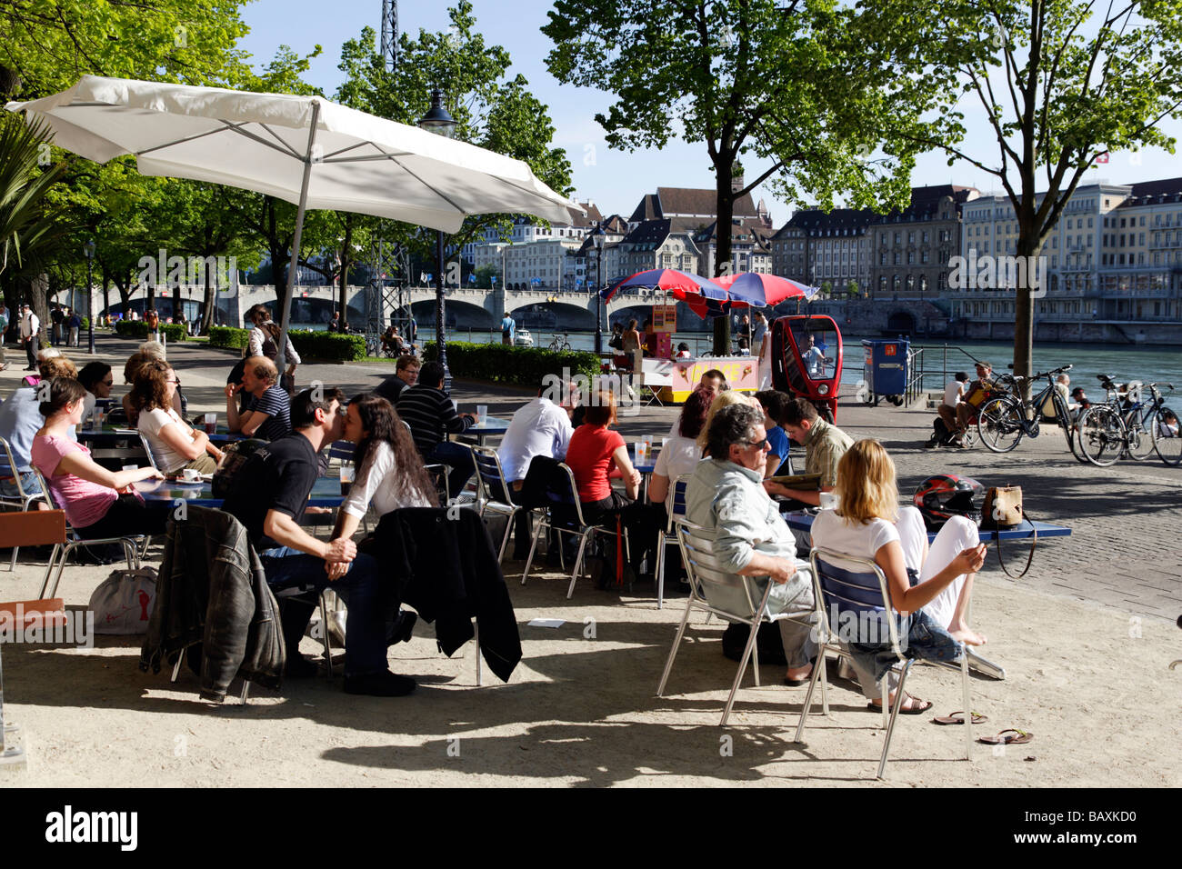 People at a cafe along the banks of the River Rhine, Riviera Klein-Basel, Basel, Switzerland - Stock Image