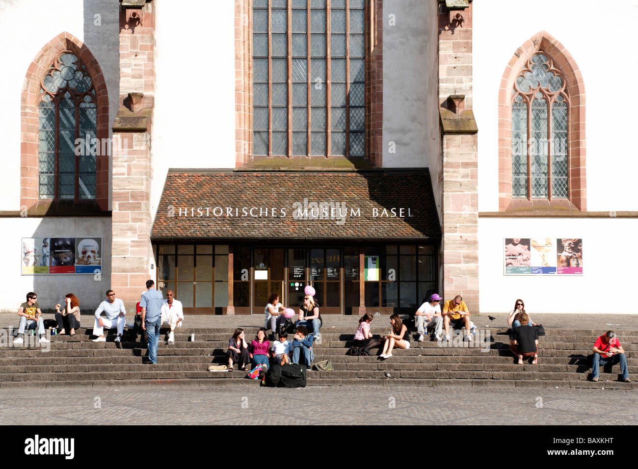 A group of young people sitting on steps in front of a church, Barfuesser Church, Historical Museum, Barfuesserplatz, - Stock Image