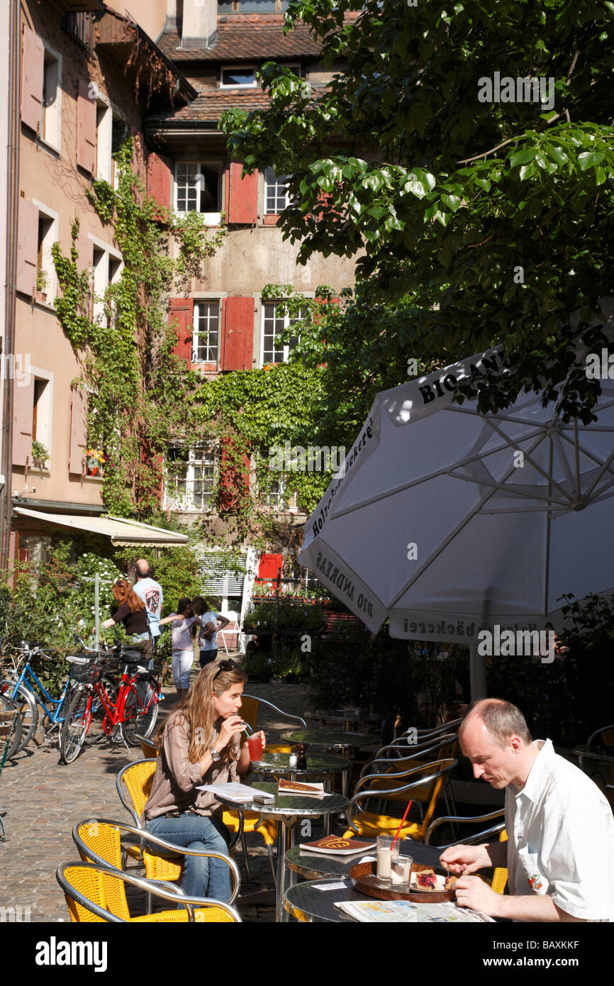 People sitting in a cafe at Andreasplatz, Basel, Switzerland - Stock Image