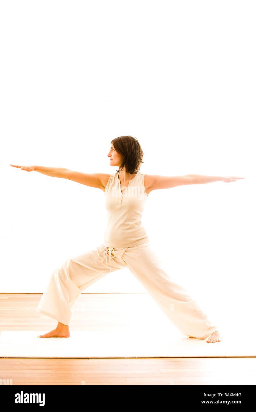 Mid adult woman practising yoga (Warrior Pose), yoga studio at Linz, Austria - Stock Image