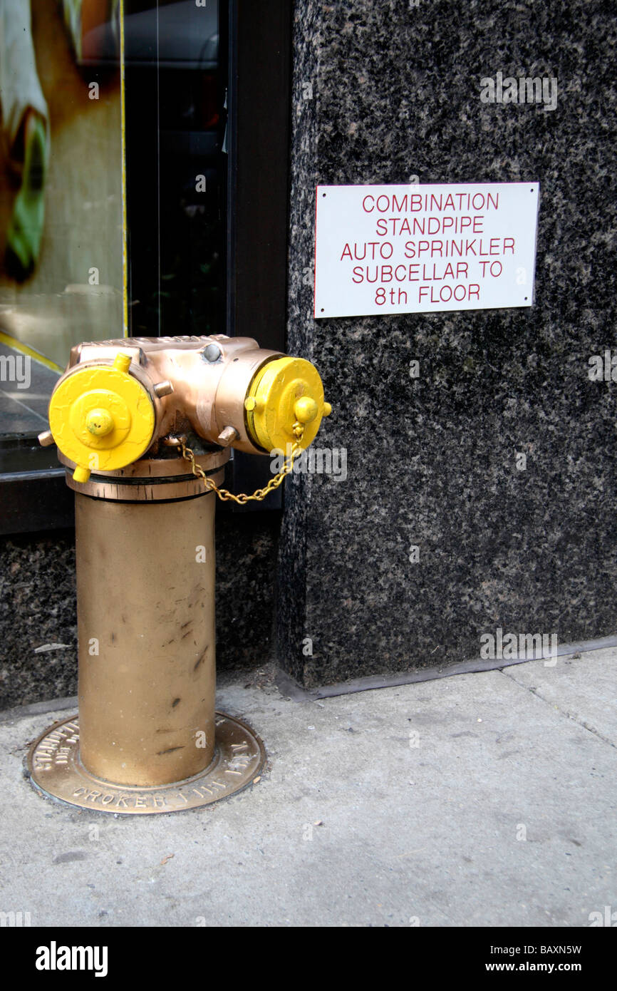 A yellow fire dry riser outside a building in New York. - Stock Image