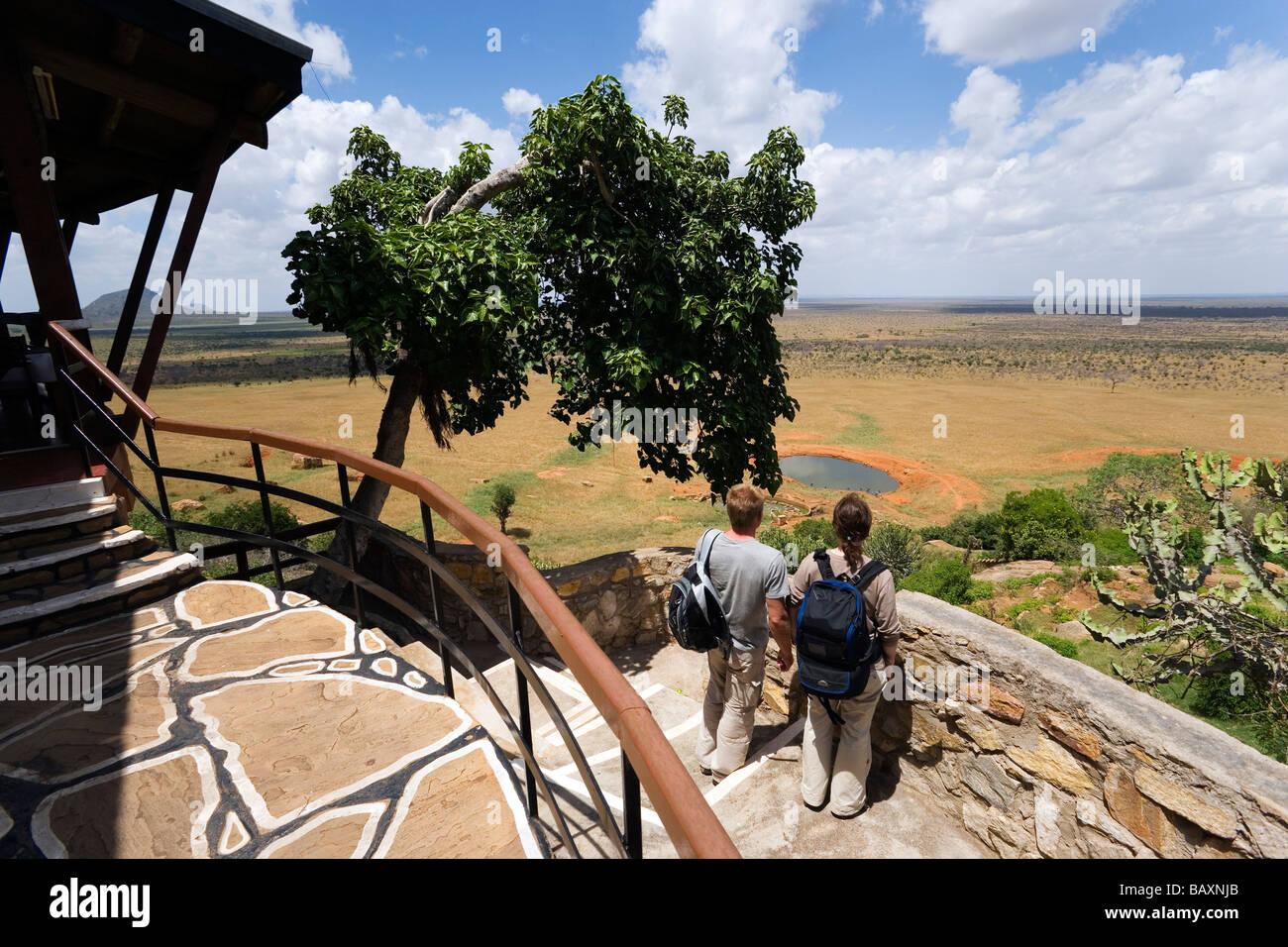 Guests looking over waterhole to savannah, Voi Safari Lodge, Tsavo East National Park, Coast, Kenya - Stock Image