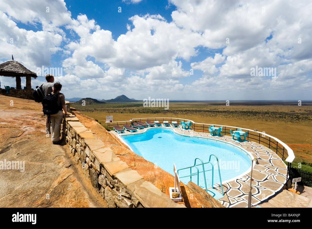 Guests looking over swimming pool to savannah, Voi Safari Lodge, Tsavo East National Park, Coast, Kenya - Stock Image