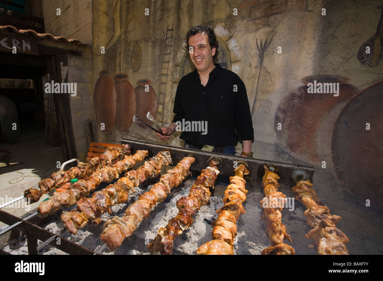 Agis Jacovides, managing director, at a charcoal grill full of quails, The Village Tavern, Pano Platres, South Cyprus, - Stock Image
