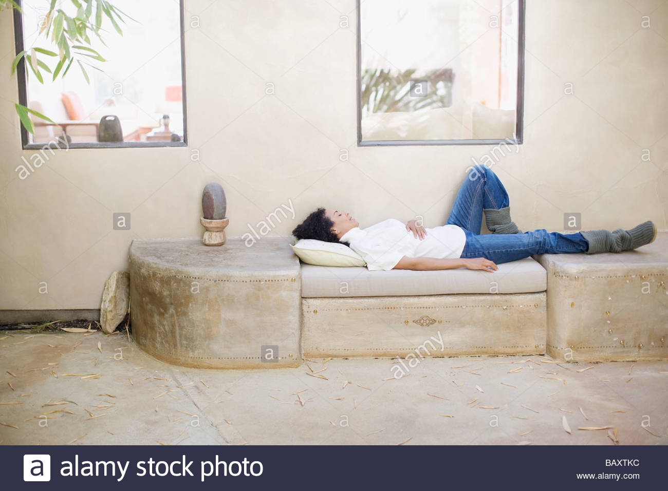 Woman laying on outdoor furniture - Stock Image