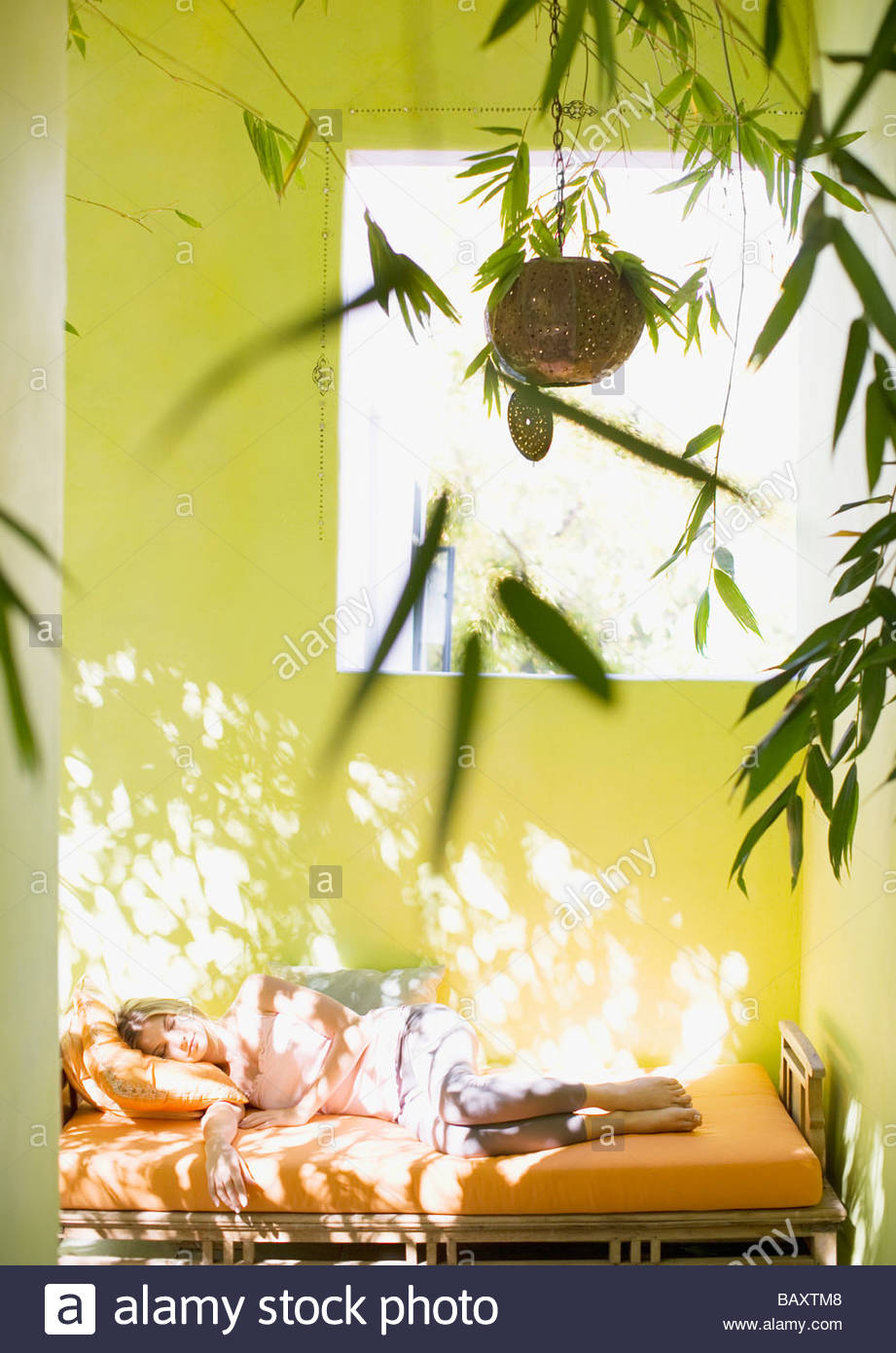 Woman sleeping on daybed in daytime - Stock Image