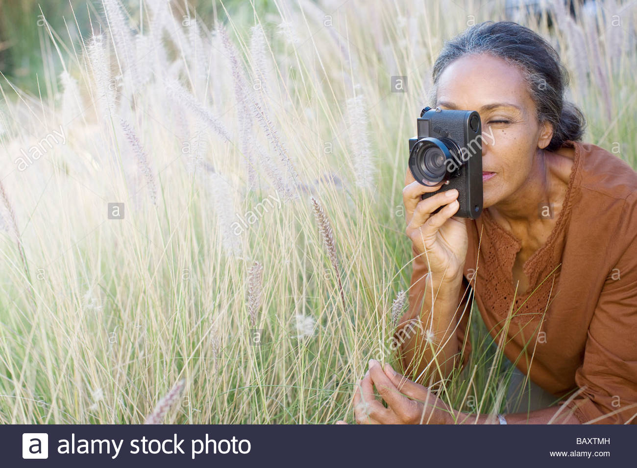 African woman taking photographs outdoors - Stock Image