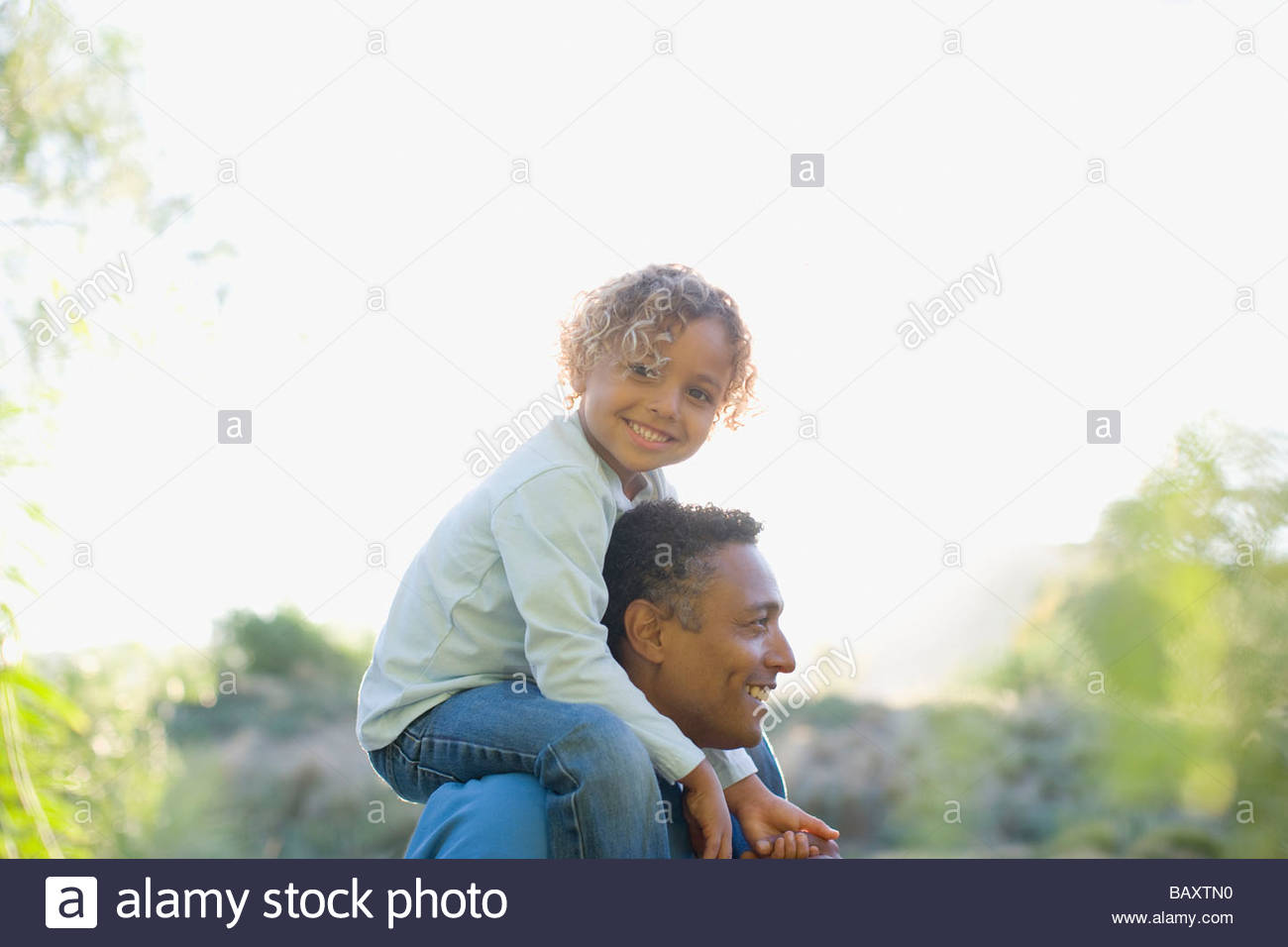 African boy sitting on father's shoulders - Stock Image