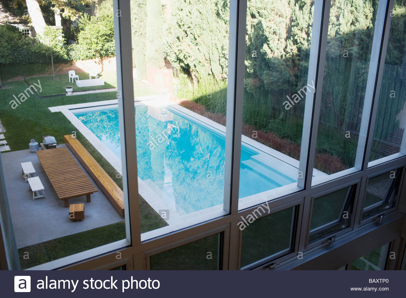 Exterior of modern house, swimming pool and patio - Stock Image