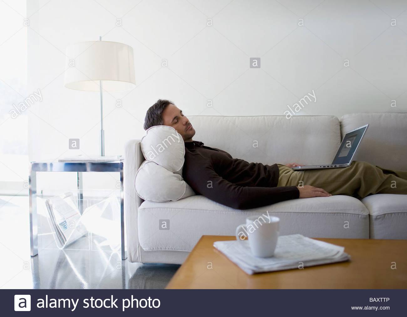 Man with laptop sleeping on sofa - Stock Image
