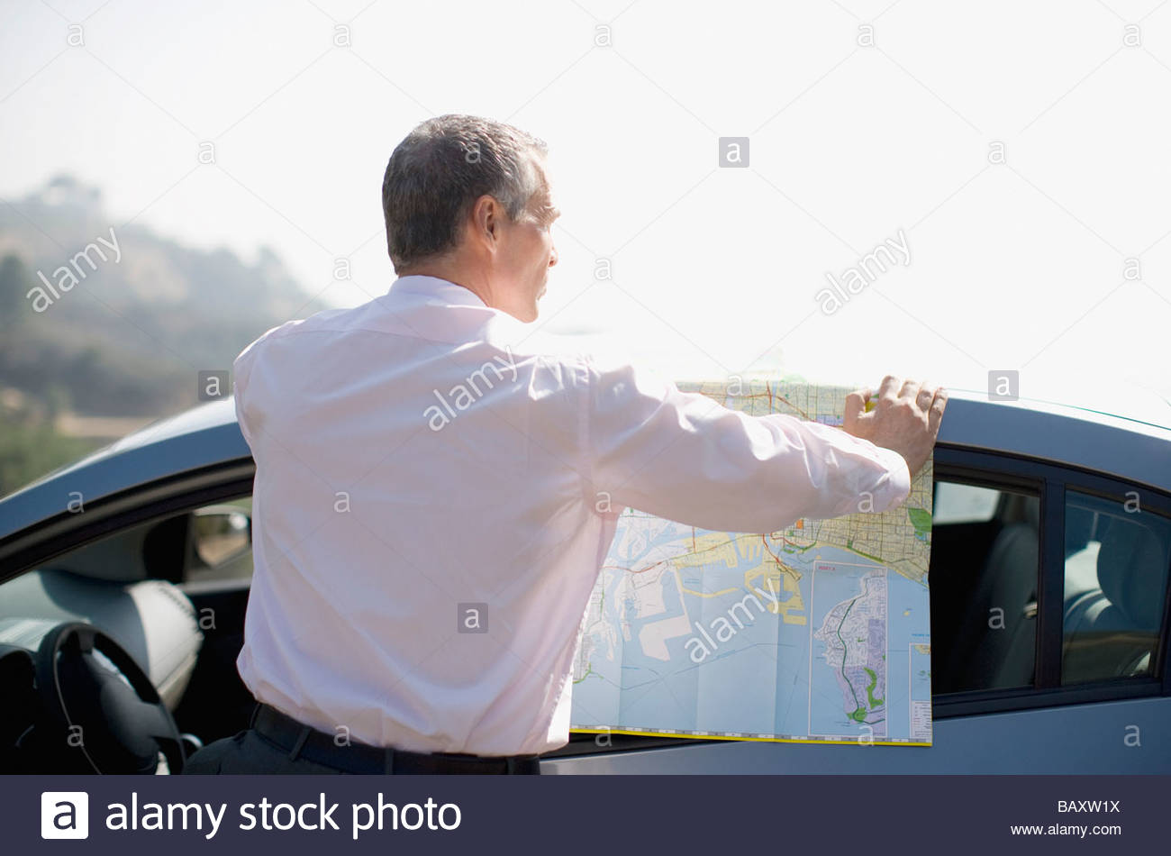 Businessman looking at map - Stock Image