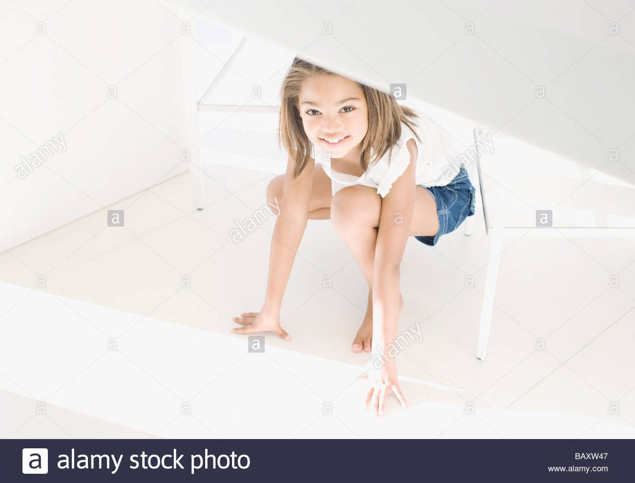 African girl crouching and smiling - Stock Image