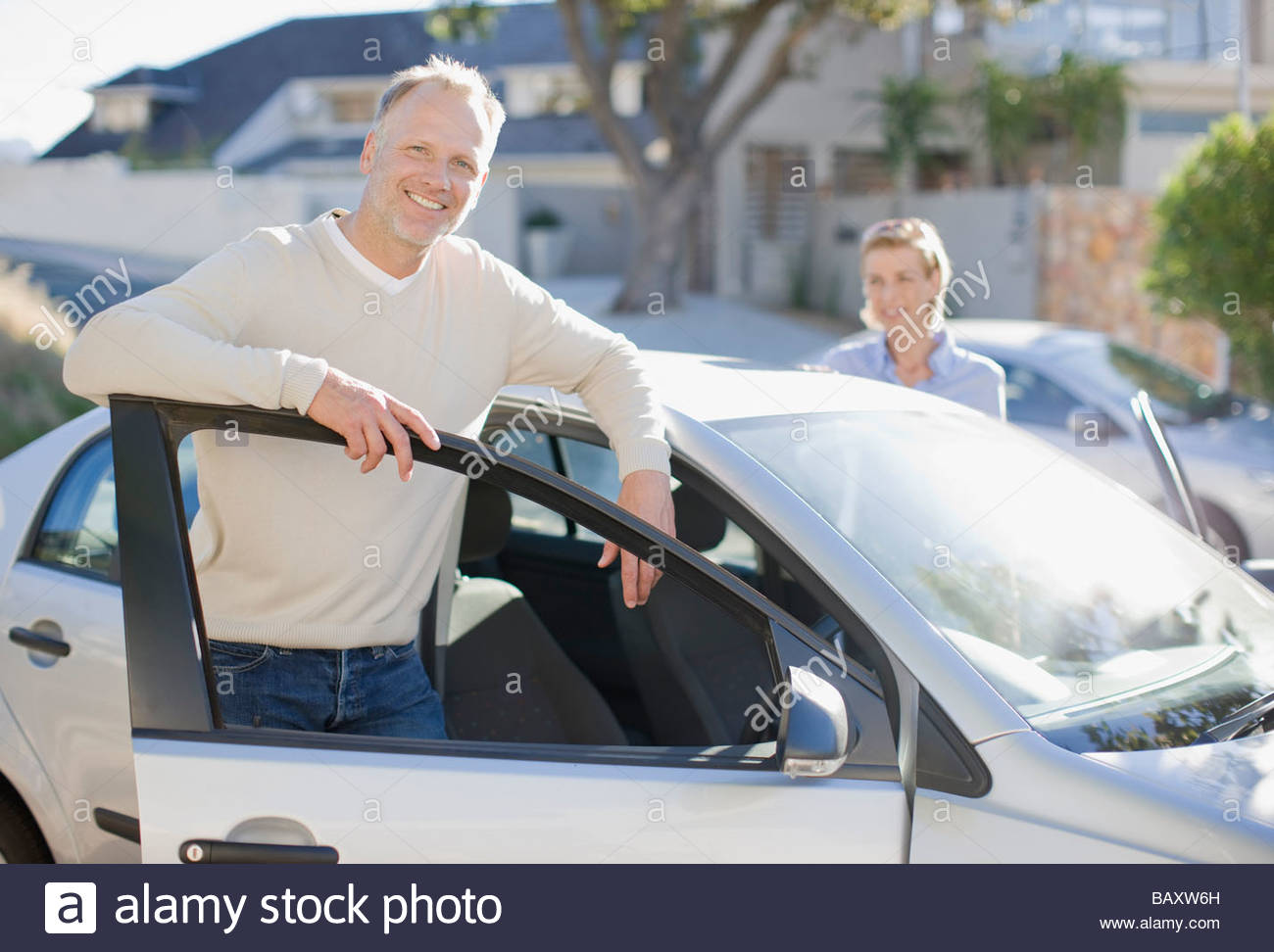 Mature couple getting into car - Stock Image