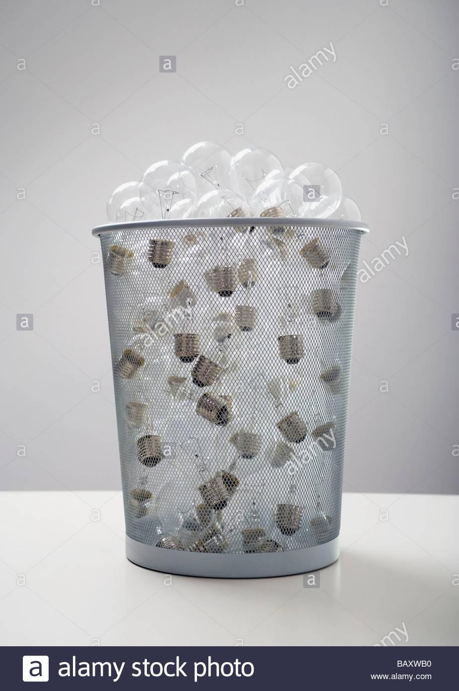Wastebasket full of old-fashioned light bulbs Stock Photo