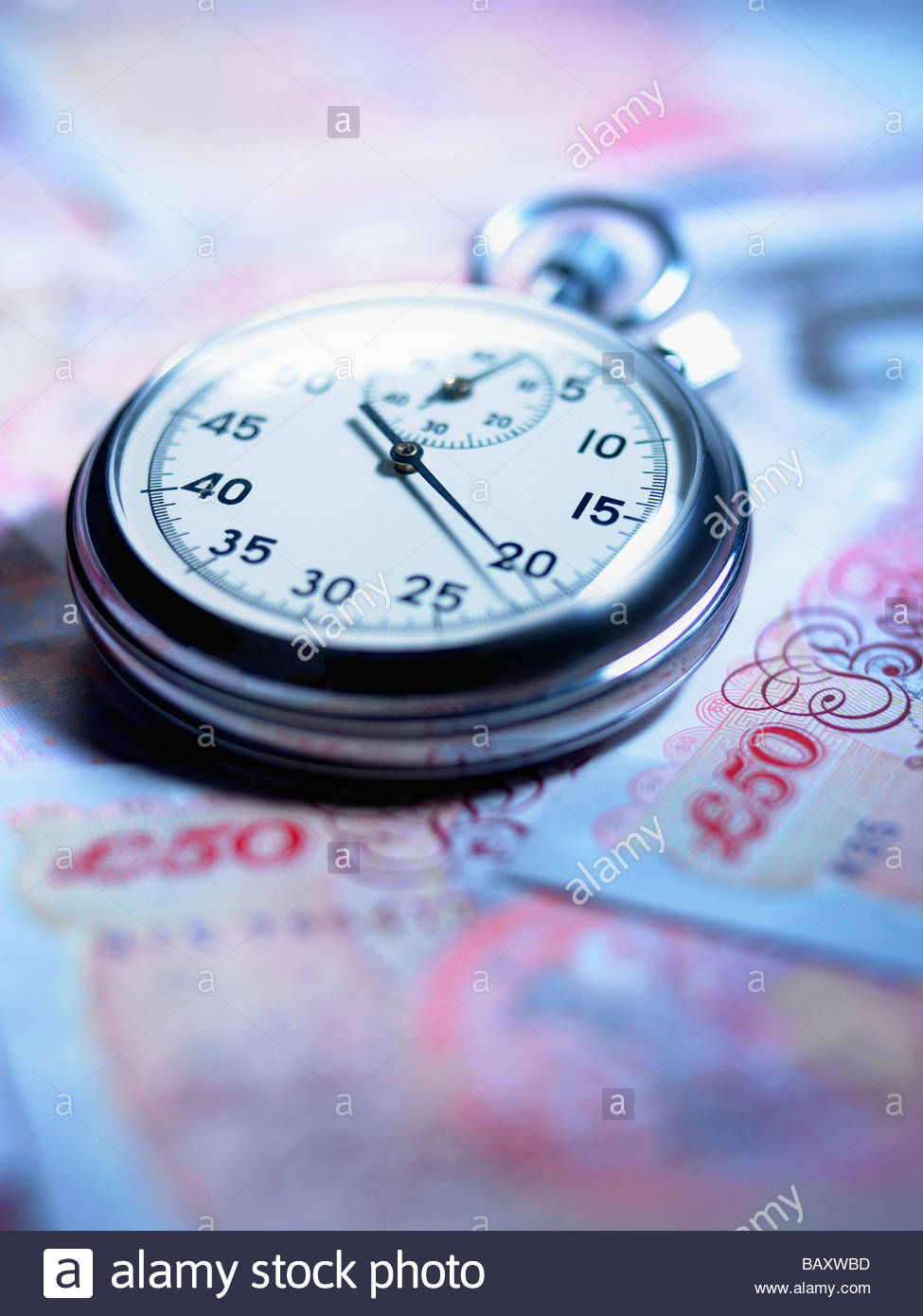 Close up of stopwatch on 50 pound notes - Stock Image