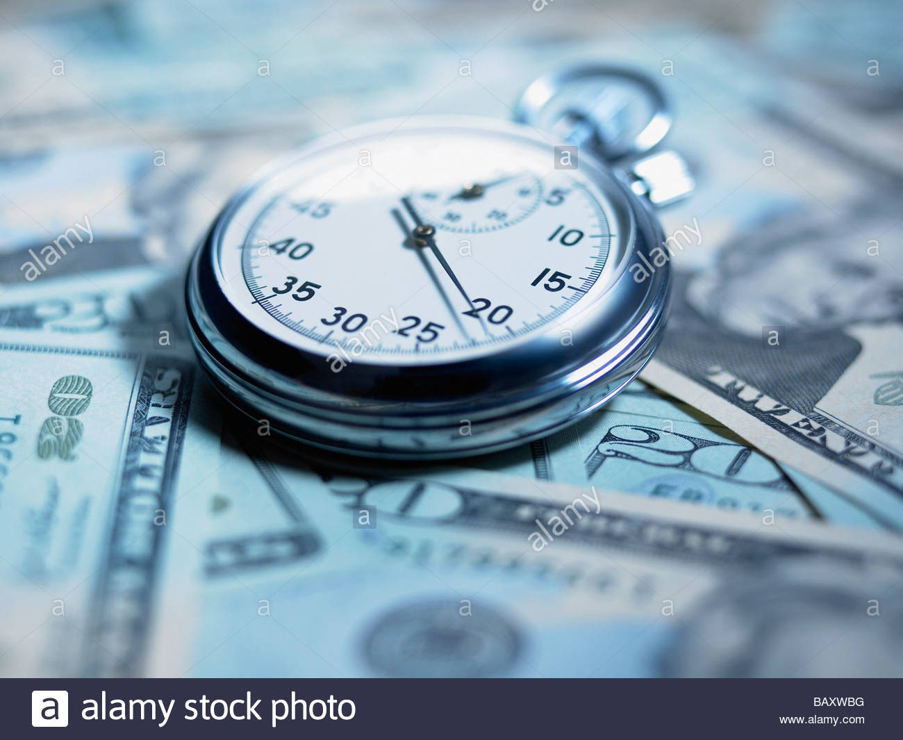 Close up of stopwatch on 20 dollar bills - Stock Image