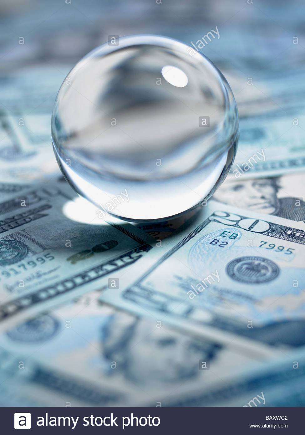 Close up of crystal ball on 20 dollar bills - Stock Image