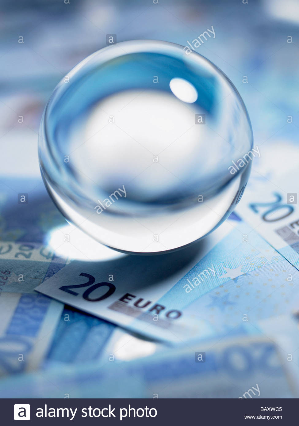 Close up of crystal ball on 20 euro notes - Stock Image