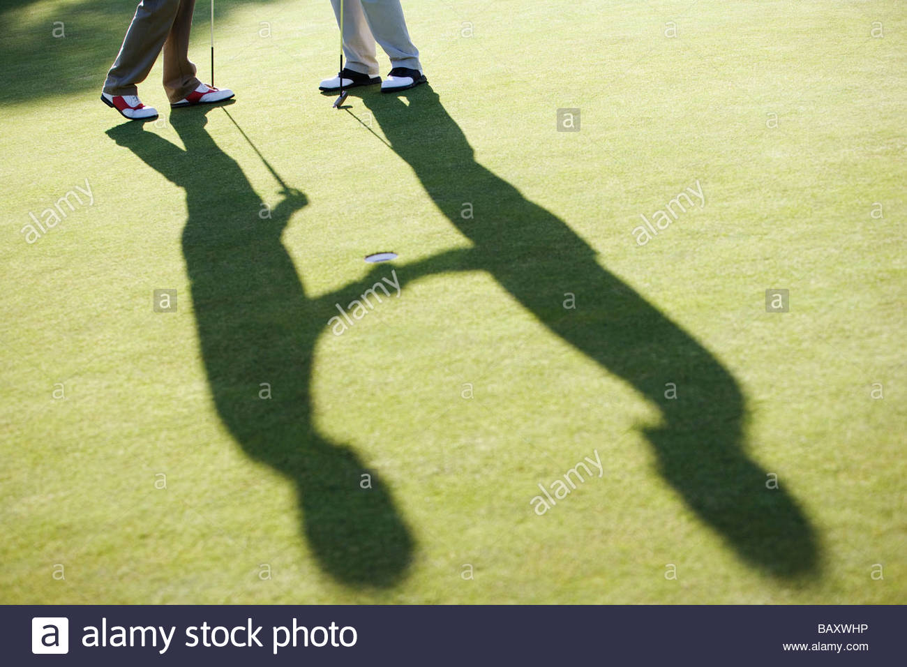Men shaking hands on putting green - Stock Image