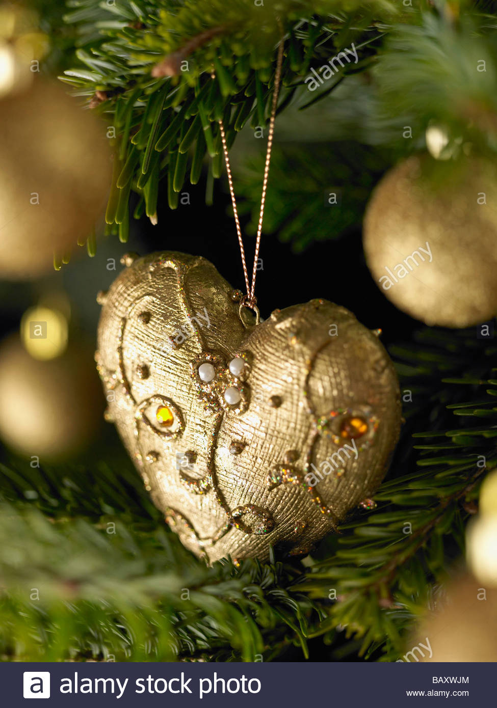 Close up of gold Christmas ornaments on tree - Stock Image