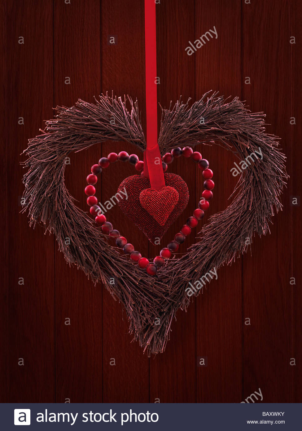 Red heart wreath hanging on door - Stock Image