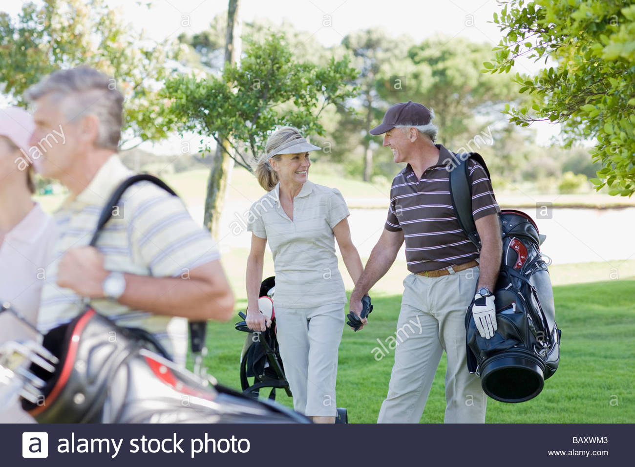 Mature couple holding hands and carrying golf bags - Stock Image