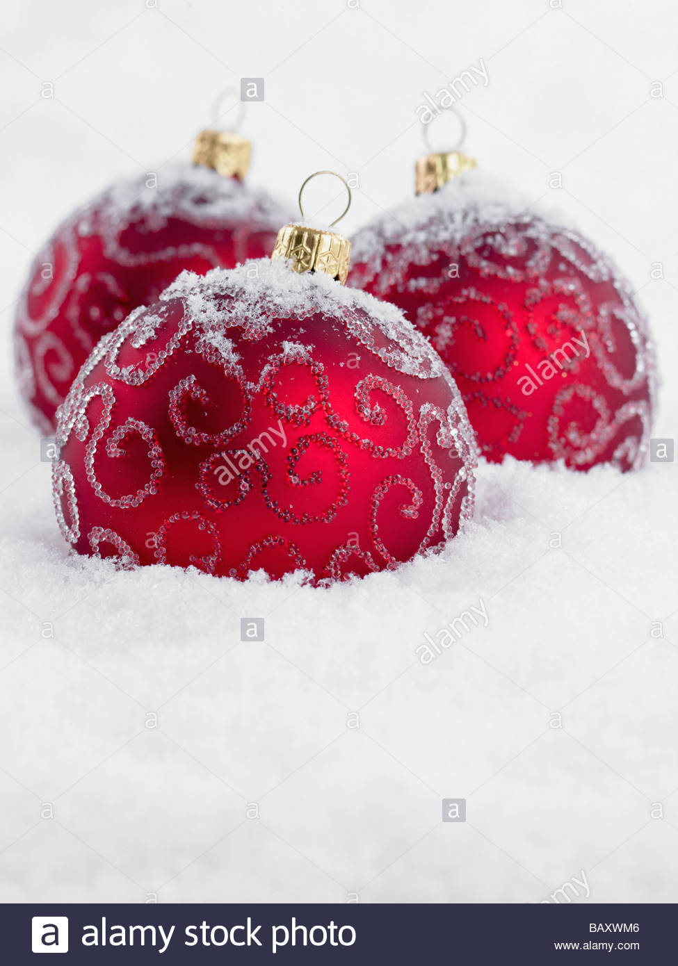 Close up of red Christmas ornaments in snow - Stock Image