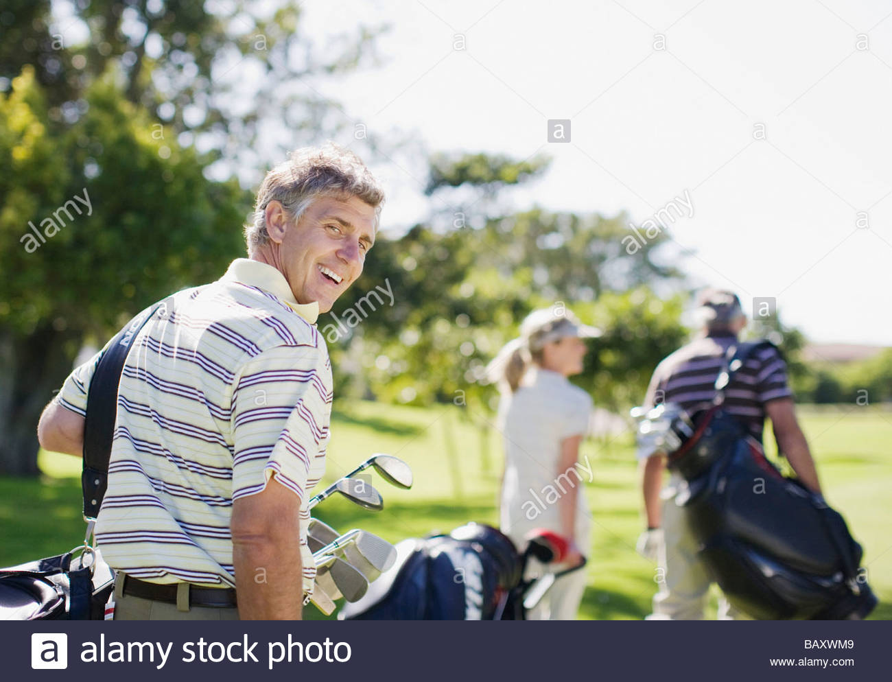 Friends carrying golf bags - Stock Image