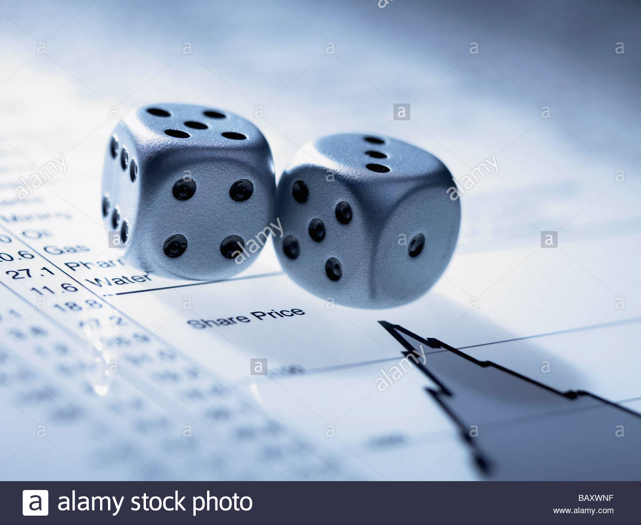 Silver dice on list of share prices - Stock Image