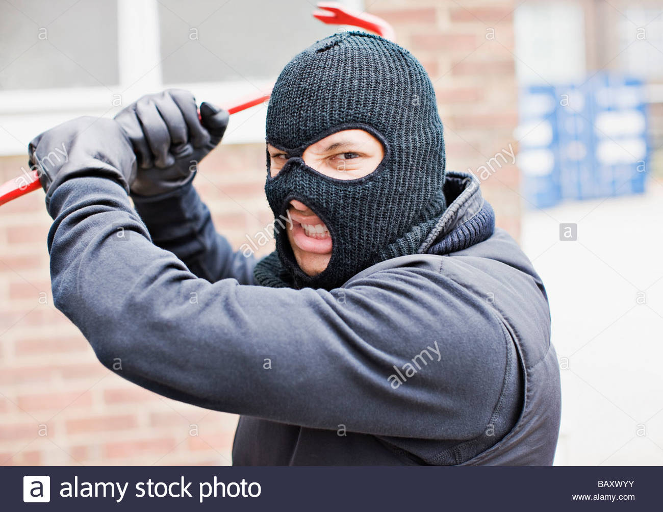 Burglar in ski mask wielding crowbar Stock Photo