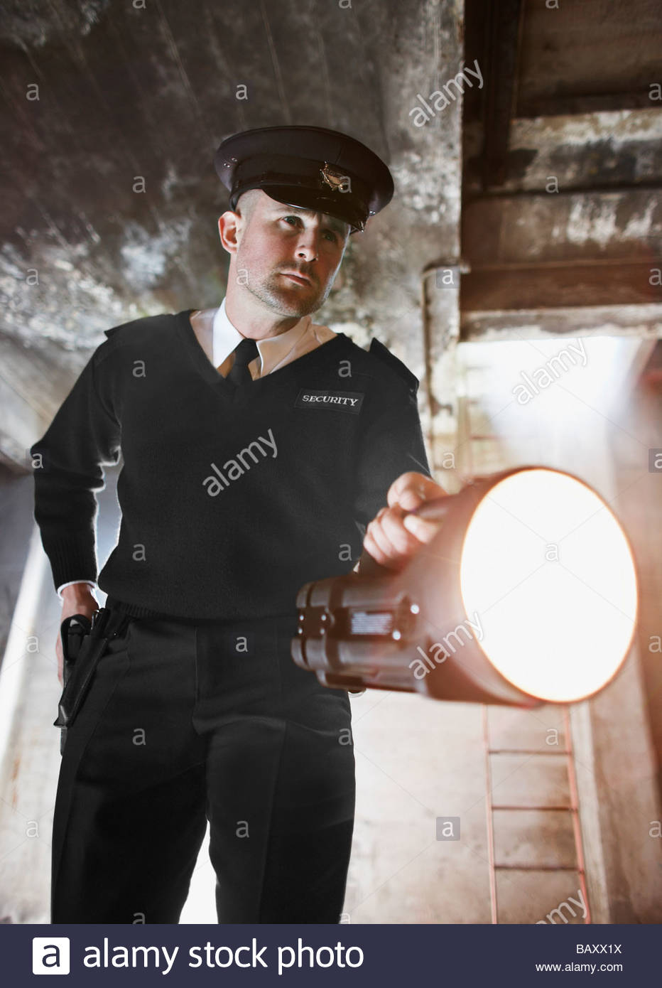 Security guard shining flashlight into bunker - Stock Image