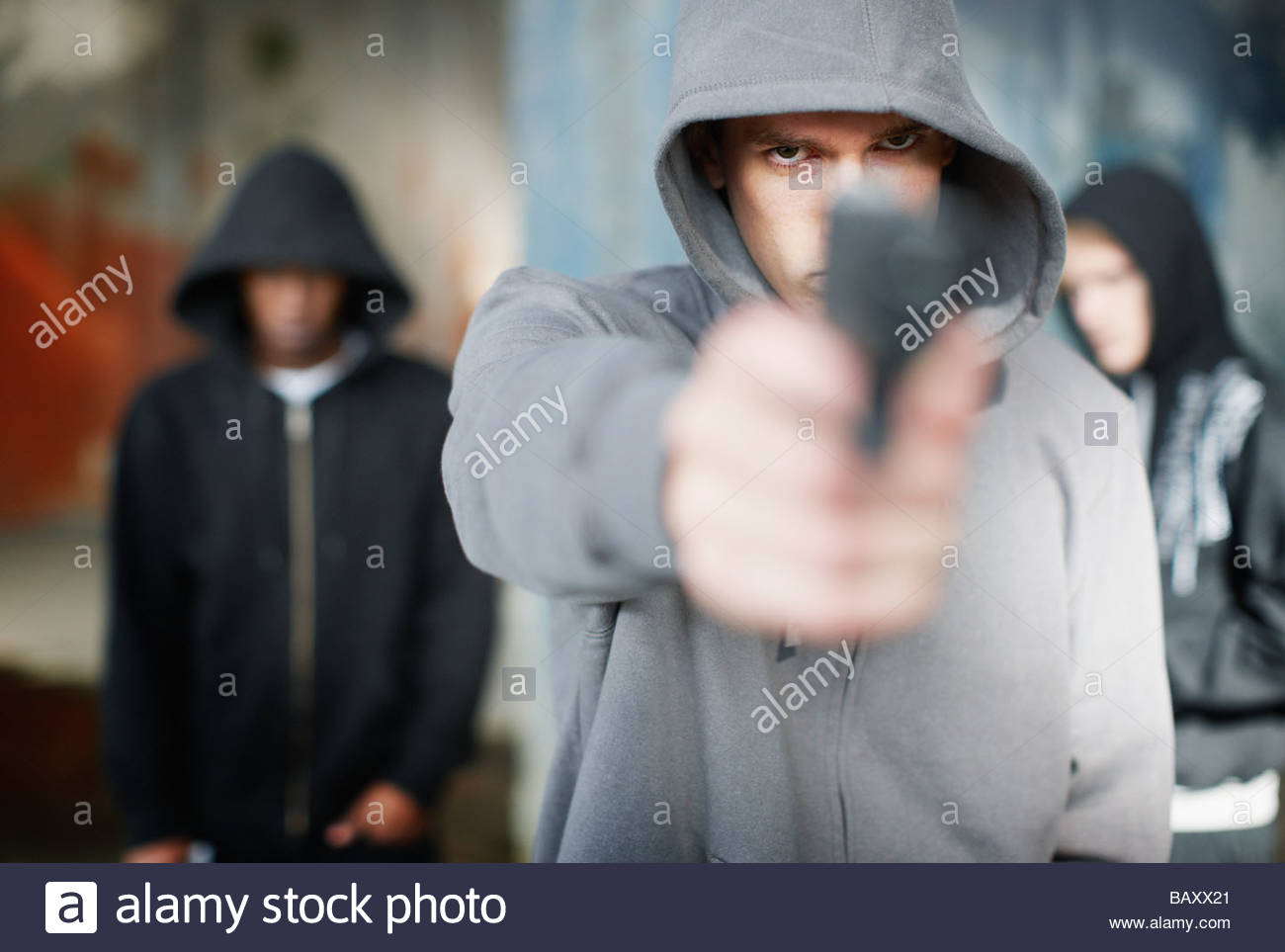 Man with gun pointed at viewer - Stock Image