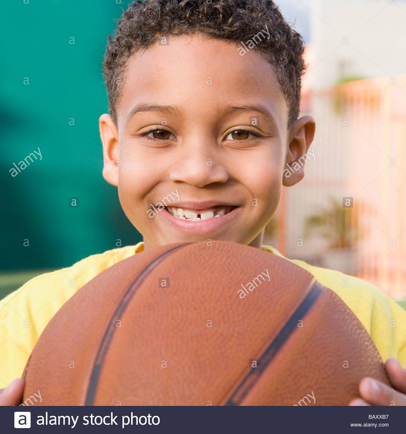Smiling boy holding basketball Stock Photo