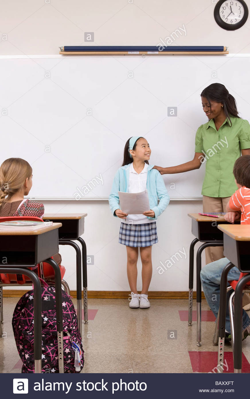Girl reading report aloud in classroom - Stock Image