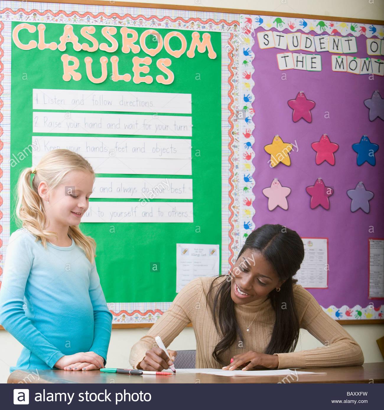Teacher grading girl's paper in classroom - Stock Image