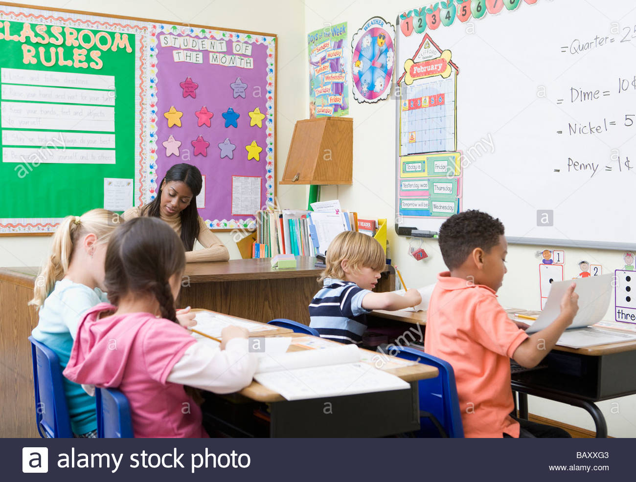 Students sitting at desks in classroom - Stock Image