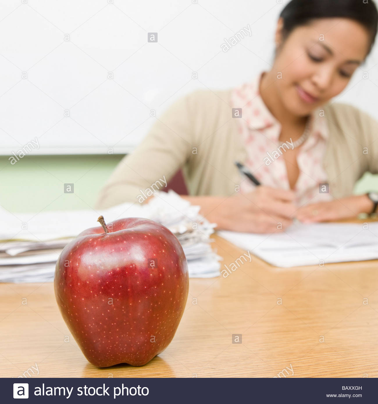 Teacher grading papers with apple in foreground - Stock Image