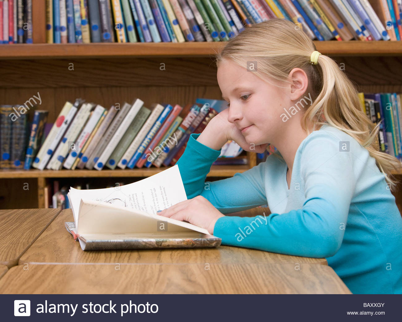 Girl reading book in school library - Stock Image