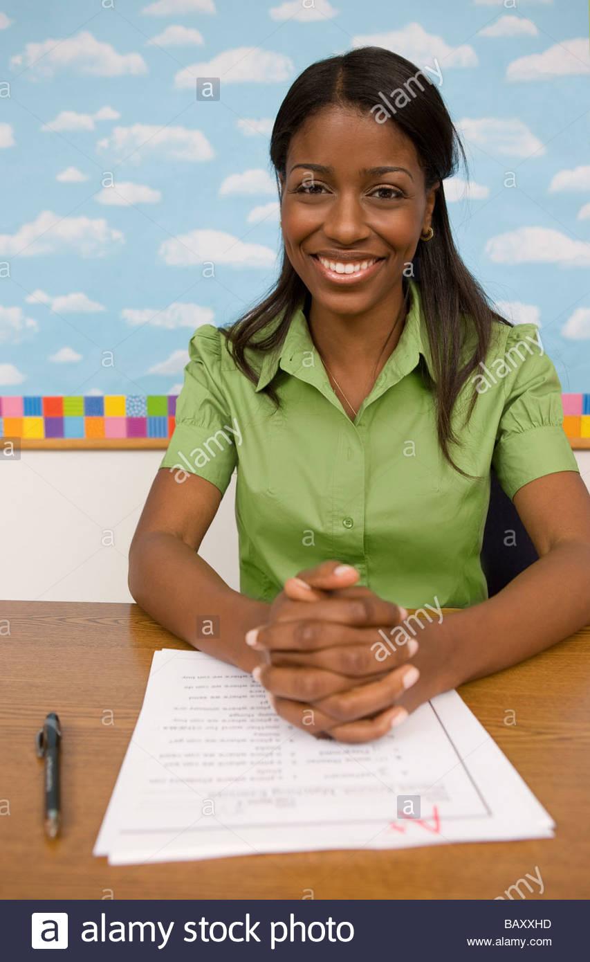 Teacher sitting at desk grading papers - Stock Image