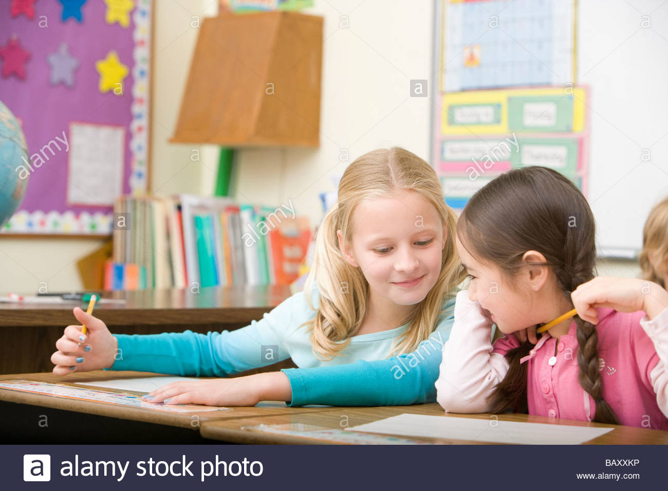Girl cheating from friend's paper on test - Stock Image
