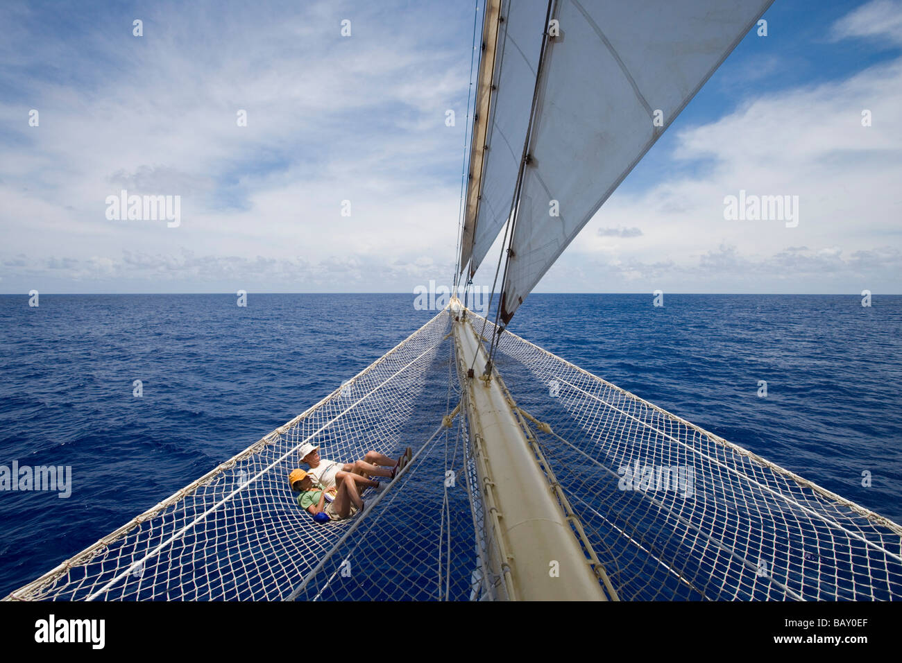 Couple relaxing in bowsprit net of sailing Cruiseship Star Flyer (Star Clippers Cruises), Bora Bora, Society Islands, - Stock Image